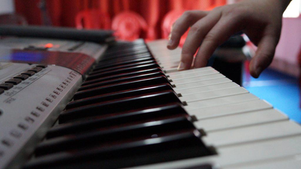 Kid plays keyboard